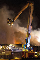 © Licensed to London News Pictures . 13/03/2013 . Alderley Edge , Cheshire , UK . Fire crew on an elevated platform work to extinguish flames which have burned out the roof at the rear of the venue . Famous celebrity nightclub , Panacea , in Alderley Edge , is ablaze tonight (12th March) . Fire crews and police were initially called to the venue at 22:30 on Tuesday night (12th March) . Around 50 fire-fighters from Cheshire and Greater Manchester worked to control the fire at the venue , which is adjacent to a petrol station and residential properties in the affluent village of Alderley Edge . This is the second time in five years the venue has been destroyed by fire , previously following a £3.2 million refurbishment in September 2008 . Photo credit : Joel Goodman/LNP