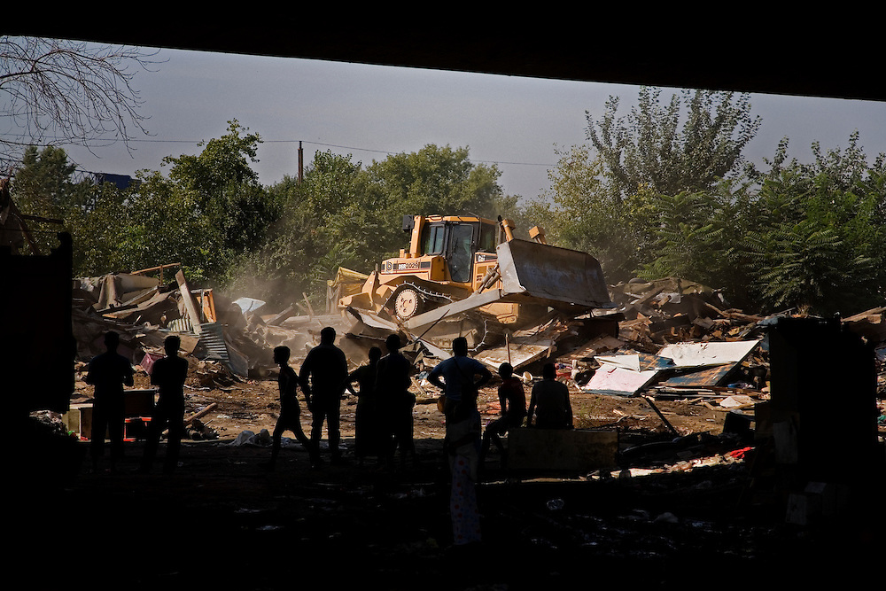 Bulldozers flatten homes in the Nova Gazela settlement while families, social workers and police watch from under the Gazela bridge.