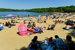 © Licensed to London News Pictures. 25/05/2020. LONDON, UK.  People take advantage of the easing of certain coronavirus pandemic lockdown restrictions to enjoy the sunshine and warm weather on Bank Holiday Monday at the beach at Ruislip Lido in north west London. The UK government continues to remind the public adhere to social distancing when outdoors and to wear a face covering where social distancing is not possible.  The forecast is for temperatures to rise to 25C, with similar conditions for the next few days.  Photo credit: Stephen Chung/LNP