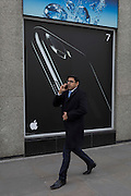 A smartphone user walk past an advert for the Apple iPhone7, on 16th February 2017, in the City of London, England.