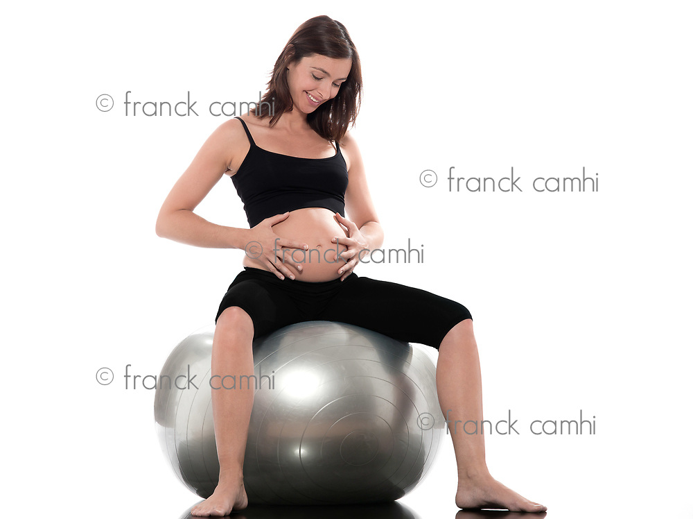 pregnant caucasian woman sitting on swiss ball isolated studio on white background