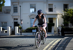 © Licensed to London News Pictures. 24/07/2018. London, UK. A cyclist passes a bridge in Little Venice in central London, as warm temperatures in the capital continue. Forecasters are predicting record temperatures later this week. Photo credit: Ben Cawthra/LNP