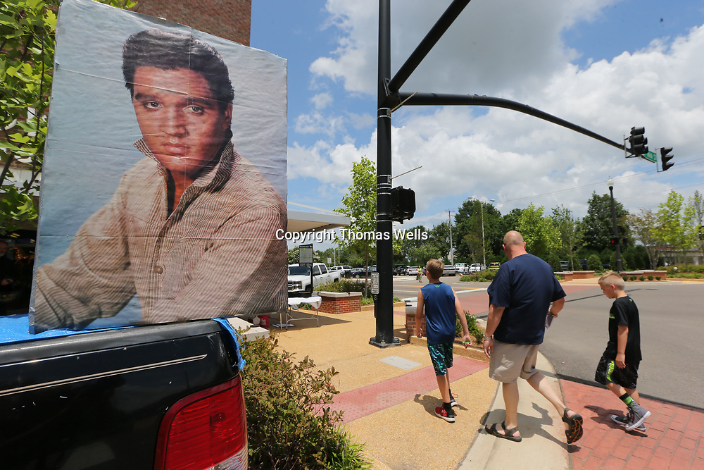 Elvis Presley Festival goers were greeted with a huge portriat of he young king as they make their way down Main Street in Tupelo on Saturday during the live music portion of the festival.