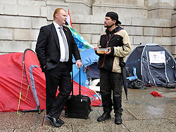 © Licensed to London News Pictures. 26/10/2011. London, UK. A protester and a man dressed in a business suit talk whilst protesters start to move tents and reorganise their site to facilitate the reopening of St Paul's. Occupy London protesters outside St Paul's Cathedral today, 26 October 2011. The UK's most popular Cathedral still has its doors closed over health and safety fears for it's visitors. Photo: Stephen Simpson/LNP
