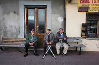 SOVERIA MANNELLI, ITALY - 17 NOVEMBER 2016: Elderly men sit on a bench by the main square in Soveria Mannelli, Italy, on November 17th 2016.<br /> <br /> Soveria Mannelli is a mountain-top village in the southern region of Calabria that counts 3,070 inhabitants. The town was a strategic outpost until the 1970s, when the main artery road from Naples area to Italy's south-western tip, Reggio Calabria went through the town. But once the government started building a motorway miles away, it was cut out from the fastest communications and from the most ambitious plans to develop Italy's South. Instead of despairing, residents benefited of the geographical disadvantage to keep away the mafia infiltrations, and started creating solid businesses thanks to its administrative stability, its forward-thinking mayors and a vibrant entrepreneurship numbering a national, medium-sized publishing house, a leading school furniture manufacturer and an ancient woolen mill.