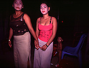 Phnom Penh, Cambodia. Prostitutes in brothel in Tuol Kork district. The girls here make US$30 a month, working on average 6 clients a day. Young children like the boy behind them, exposed to the sex industry, frequently grow up to become involved in the industry.<br />