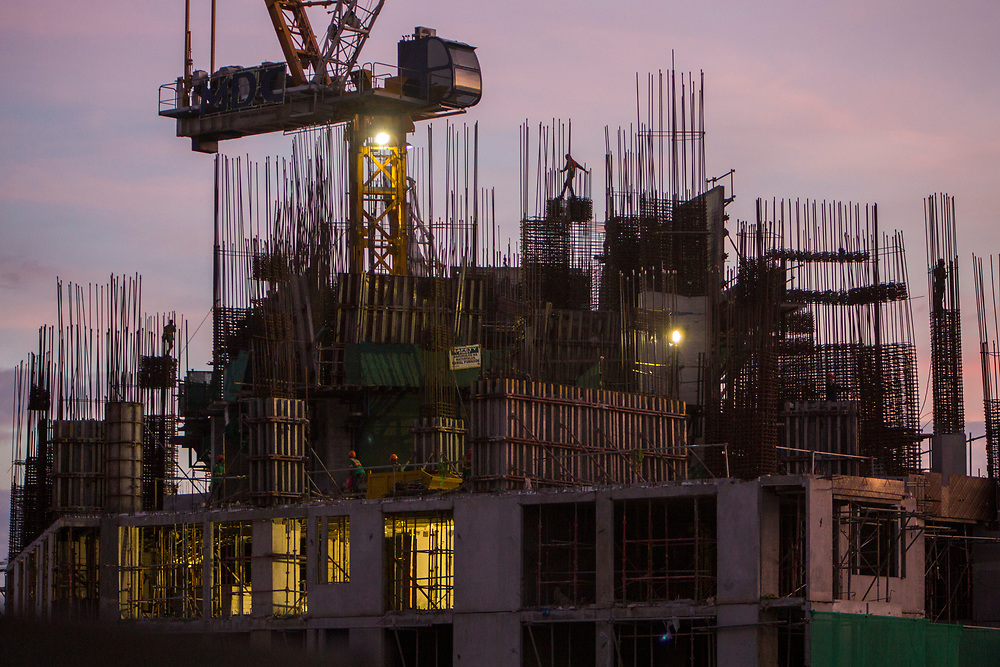 Construction workers work without safety gear on top of Garden Towers under construction at dusk on East Street, Makati, Metro Manila, Philippines.  (photo by Andrew Aitchison / In pictures via Getty Images)
