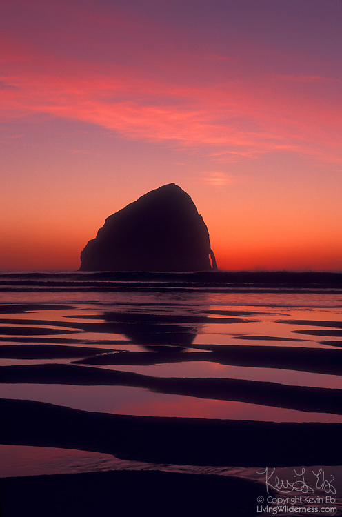 The setting sun colors the sky above Haystack Rock, a prominent sea stack located off the coast of Cape Kiwanda near Pacific City, Oregon.