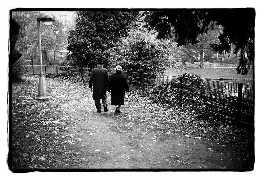 An elderly couple walks in the city park of Antwerp, Belgium