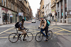 Glasgow, Scotland, UK. 26 March, 2020. Views from city centre in Glasgow on Thursday during the third day of the Government sanctioned Covid-19 lockdown. The city is largely deserted. Only food and convenience stores open. Pictured; Two Deliveroo delivery cyclists pause for a portrait .Iain Masterton/Alamy Live News