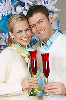 Couple toasting champagne glasses by Christmas tree, portrait