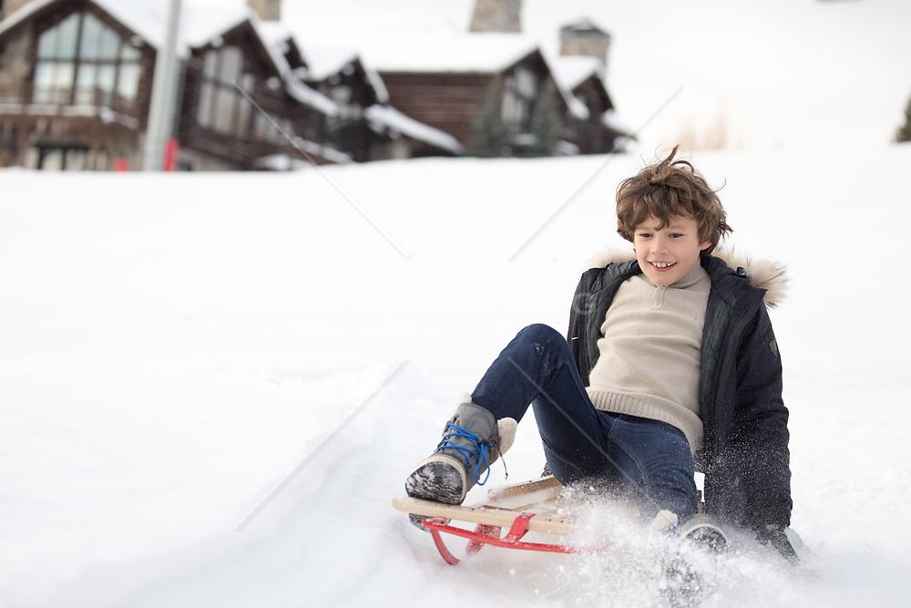 boy enjoying a sled ride down a snowy mountain