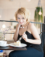 Portrait of happy young woman eating cake at cafe