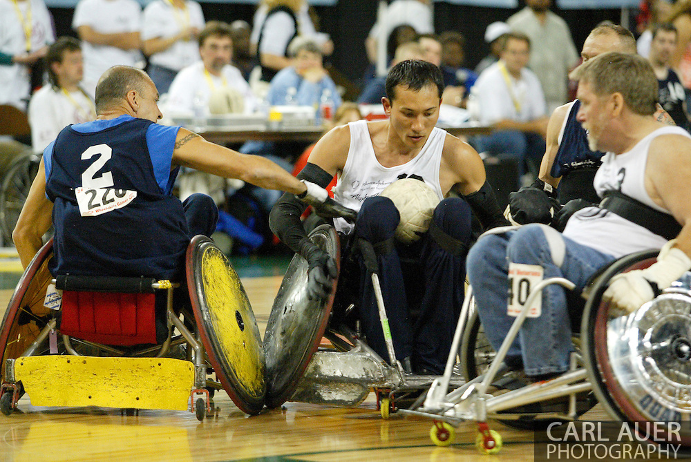 July 7th, 2006: Anchorage, AK - William Groulx (10) tries to get past a teammate and David Hosick (2) as White defeats Blue in the gold medal game of Quad Rugby at the 26th National Veterans Wheelchair Games.