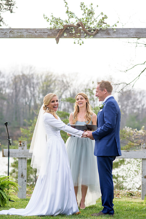 Annapolis, Maryland - April 18, 2015: Hannah North leads the exchanging of vows  for her lifelong friend Stephanie Shearer Cate and her groom Winston Bao Lord at the home of Jeff and Marry Zients' in Annapolis, Maryland Saturday April 18, 2015. The trio laugh after Hannah mistakenly said the name of her three-year-old daughter, &quot;Salem,&quot; instead of Stephanie. <br /> <br /> <br /> <br /> CREDIT: Matt Roth for The New York Times<br /> Assignment ID: 30173318A