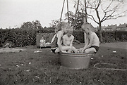 Children sitting on the edge of a small tub.