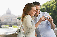 Couple on bridge looking at pictures on digital camera in Rome Italy