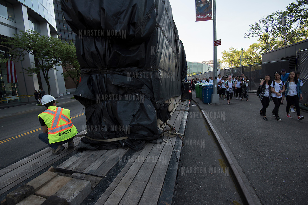 "May 26, 2015 - New York, NY : Cedric Revest of Show Canada Inc., at left, oversees the delivery of four fiberglass fish (in crates on flatbed truck under black tarps), to Seaglass Carousel in Battery Park on Tuesday morning, May 26. A project of The Battery Conservancy, the Seaglass Carousel, which is set to open in mid-July, is a creation of WXY Architecture and George Tsypin Opera Factory. The carousel will feature thirty fiberglass fish ranging in height from 13'7"" to 3'9"". CREDIT: Karsten Moran for The New York Times"