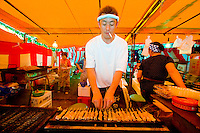 A food stall cook puffs on a cigarette while BBQing skewered strips of meat.