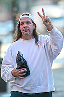 Man flashes me the peace sign while carrying a bottle of booze in the Lower East Side, NYC
