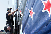 Emirates Team New Zealand sailor Blair Tuke helps with raising the main on the practice day of the Land Rover Extreme Saling Series regatta in Qingdao China. 30/4/2014
