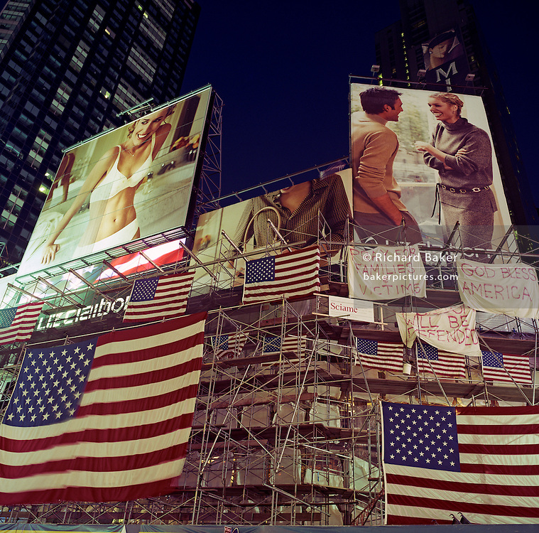 Lit by the bight lights of Times Square in New York City, US flags hang from the scaffolding of a construction site four days after the attacks on the World Trade Center on September 11th. Above the Stars and Stripes, we see fashion advertising bllboards showing white American models posed in contemporary couture proving that business and the media works endlessly to provide content and commerce amid the emotional turmoil and horrors of the terrorist attacks. Large white sheets pronounce prayers for the families of victims and to God Bless America.