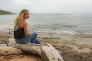 Contemplative 14 year old girl sitting on a beach