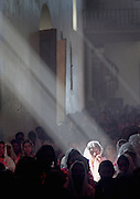 An Indian woman is caught in a beam of light caused by smoke from the incense inside the Catholic Church in Simojovel, Mexico, during Mass..Jan 12, 1006.