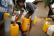 Sarah Adjrokor, 18, fills plastic containers with water from a tap in a poor neighborhood of Accra, Ghana's capital, on Monday Mar 5, 2007. Most parts of the city are plagued with intermittent water shortages, and people buy water from the few running taps. They then have to carry the containers to their homes over distances that often reach several hundred meters. Meanwhile, Ghana is preparing to celebrate its 50 years of independence from the UK on March 6th.