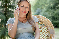 Portrait of beautiful young woman using mobile phone on seat in park