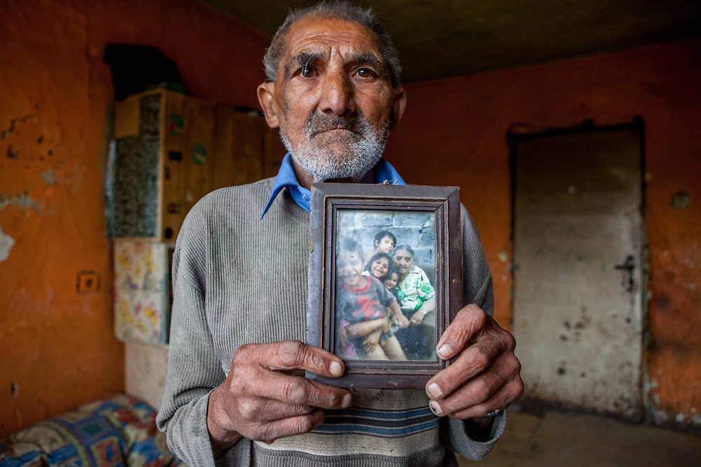 "Jan Ondic - 87 years of age (2014) - is one of the oldest inhabitants at the Roma settlement. He is holding a frame with a photograph of his beloved wife - she passed away a long time ago and now he lives by his own, but with her in his memories. He lives at the Roma part of the district ""Podsadek"". The town of Stara Lubovna has a population of 16350, of whom 2 060 (13%) are of Roma origin. The majority of Roma live in the Podsadek district, where 980 (74%) out of 1330 inhabitants are Roma."