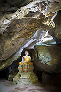 Buddha sculpture inside limestone cave, Vang Vieng, Laos