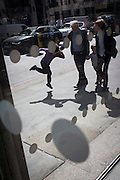 A leaping young boy walks with guardians past an office foyer entrance featuring dots and circles on exterior windows in the City of London.