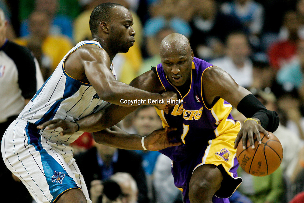April 24, 2011; New Orleans, LA, USA; Los Angeles Lakers power forward Lamar Odom (7) is defended by New Orleans Hornets power forward Carl Landry (24) during the fourth quarter in game four of the first round of the 2011 NBA playoffs at the New Orleans Arena. The Hornets defeated the Lakers 93-88.   Mandatory Credit: Derick E. Hingle