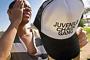 "24 MARCH 2004 - PHOENIX, AZ, USA: A member of the Maricopa County Jail's Juvenile Chain Gang wipes his brow while cleaning up a vacant lot at a worksite in Phoenix, AZ, March 24, 2004. The juveniles volunteer to serve Maricpoa County Sheriff Joe Arpaio's chain gang. The sheriff, who claims to be ""the toughest sheriff in America,"" has chain gangs in both the men's and women's jails and now has a chain gang for juveniles sentenced and serving time as adults in the county jail system. The sheriff claims it is the only juvenile chain gang in the country.   PHOTO BY JACK KURTZ"