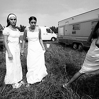 """Girls waiting before the celebration for the baptism. France, Marville, August 2002 - 40,000 Gypsies from all over the Europe come together and pray in Marville, a little village in France. They encamped in a former air base of NATO during 1 week. """"Vie et Lumiere"""" is an International Evangelic Community. ©Jean-Michel Clajot / Cosmos"""
