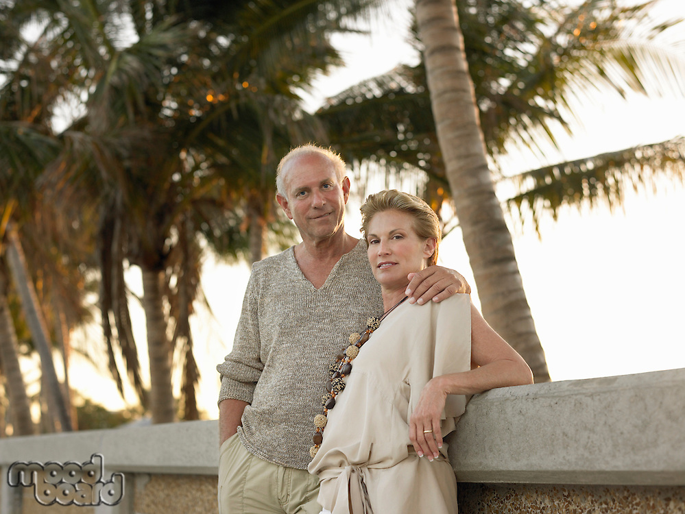 Senior couple leaning against wall palm trees in background