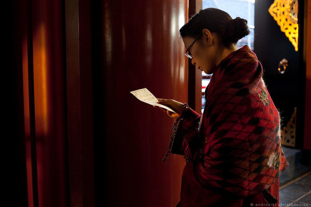 Woman in kimono reading a fortune telling paper inside Sensoji temple in Asakusa