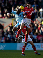 Photo: Jed Wee.<br />Nottingham Forest v Chesterfield. Coca Cola League 1.<br />31/12/2005.<br />Chesterfield's Paul Hall (L) jumps with Forest's John Thompson for possession.