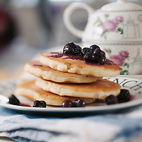 A stack of Blueberry Pancakes with sauce and butter ontop.