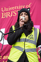 © Licensed to London News Pictures. 25/11/2019. Bristol, UK. University strike across the UK. MADHU KRISHNAN, Bristol UCU Executive member, speaks at a Rally and march by University and College Union (UCU) members at the University of Bristol with support from students. Strikers gathered outside the university's Victoria Rooms and then marched down Bristol's Park Street past the university's Wills Memorial tower. The disputes is about changes to the Universities Superannuation Scheme (USS) and universities' failure to make improvements on pay, equality, casualisation and workloads. As well as eight strike days from 25 November 2019 to Wednesday 4 December 2019, union members will begin 'action short of a strike'. This involves things like working strictly to contract, not covering for absent colleagues and refusing to reschedule lectures lost to strike action. Photo credit: Simon Chapman/LNP.