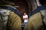 A Palestinian boy is detained by Israeli soldiers while riding his bicycle in the old city of Hebron in July 2015.
