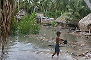 "A young boy on the South Pacific island of Kiribati, plays in the sea water during a ""king tide"", as the water encroaches on the land of his village at Buota."