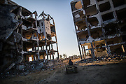 A young kid is seen driving his cart truh shiled building in Beit Hanoun northern Gaza Strip, many are trying to collect personal items and any reusable materials