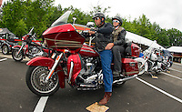 Desi and Sandy Alvarez choose a Road Glide Ultra from Harley Davidson's free demo ride setup at Hart's Turkey Farm's parking lot in Meredith Monday morning.  (Karen Bobotas/for the Laconia Daily Sun)