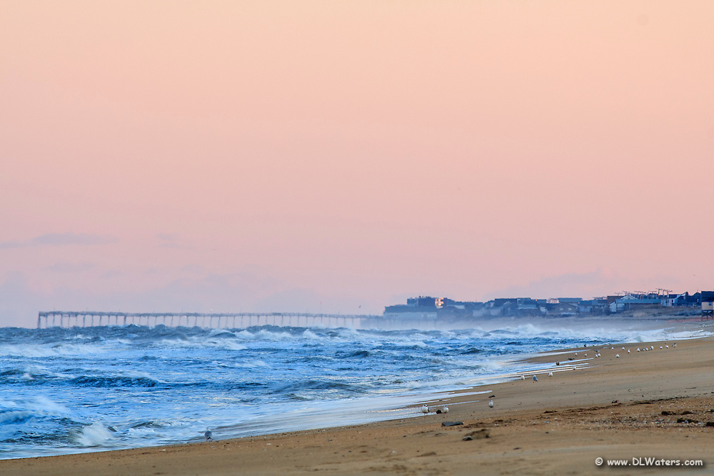 On a peach colored morning waves break on Kitty Hawk beach with Kitty Hawk pier in the distance.
