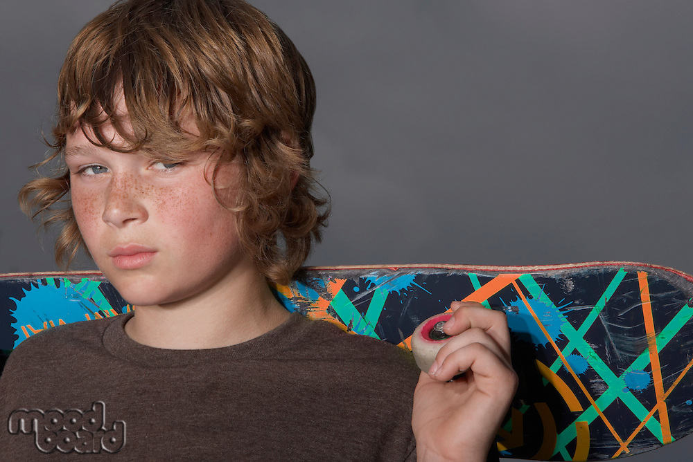 Teenage boy (13-15) holding skateboard outdoors portrait close up
