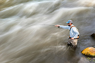 Chris Lemons fly fishes in the Roaring Fork River during heavy spring runoff in Woody Creek, Colorado.
