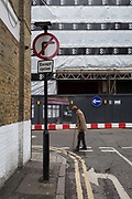 An elderly gentleman carefully crosses a street corner featuring traffic direction arrows, 7th March 2018, in London England.