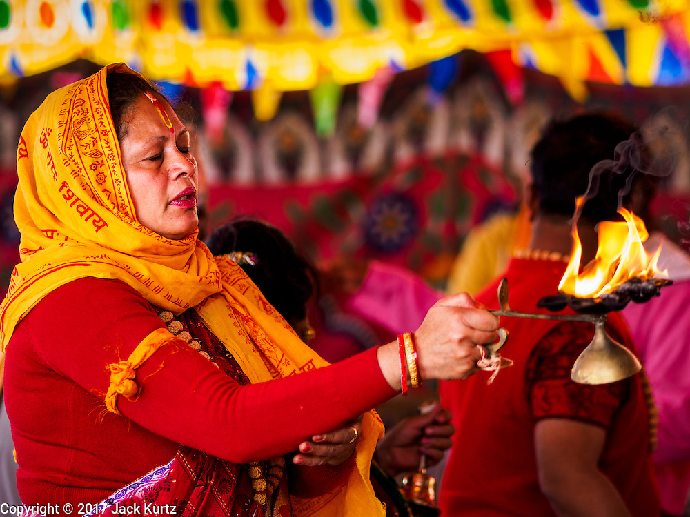 04 MARCH 2017 - KATHMANDU, NEPAL: A woman prays at a Hindu prayer service for victims of the 2015 Nepal earthquake. Recovery seems to have barely begun nearly two years after the earthquake of 25 April 2015 that devastated Nepal. In some villages in the Kathmandu valley workers are working by hand to remove ruble and dig out destroyed buildings. About 9,000 people were killed and another 22,000 injured by the earthquake. The epicenter of the earthquake was east of the Gorka district.     PHOTO BY JACK KURTZ